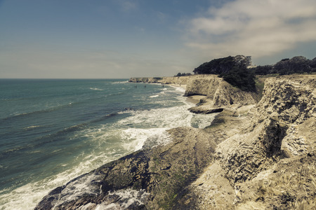 steep: Empty Beach with steep cliffs - vintage view Stock Photo