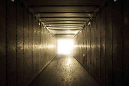 semi trailer: Empty old truck trailer with light at the end