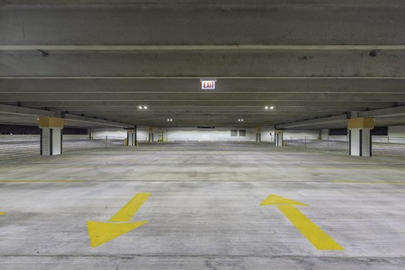 Empty parking garage with exit sign at night