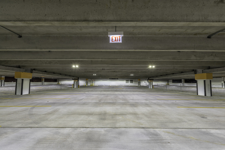 empty warehouse: Empty parking garage with exit sign at night