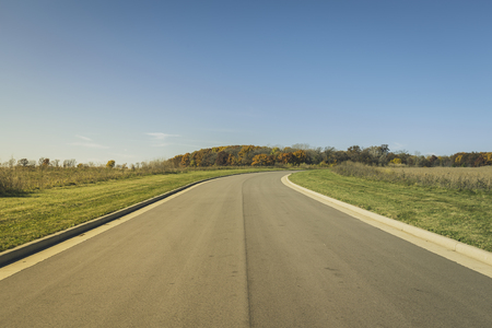subdivision: Asphalt road in new real estate subdivision- vintage colors