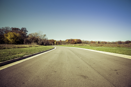 subdivision: Asphalt road in new real estate subdivision - vintage colors