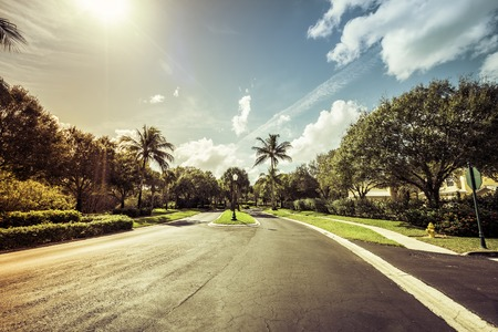gated: Gated community road in South Florida, light leaks Stock Photo