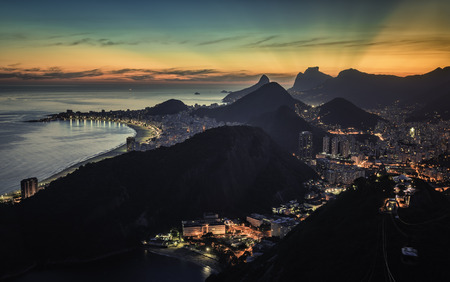 iluminated: Sunset behind the mountains with iluminated Rio de Janeiro and Copacabana Beach, Brazil Stock Photo