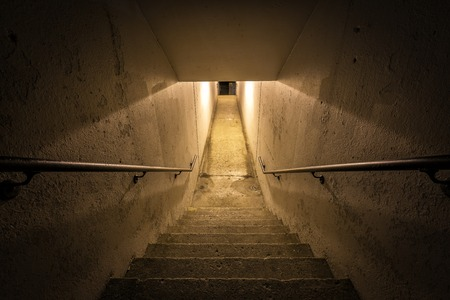 character traits: Staircase with metal handrail in empty  tunnel at night