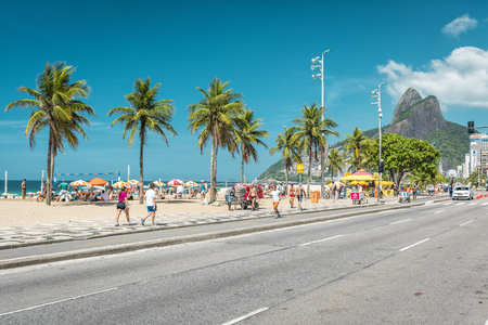 People enjoying the sun on iconic Ipanema Beach in Rio de Janeiro.