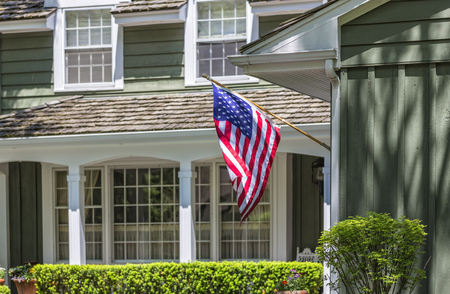 American flag wawing in front of typical american house. Fosus on flag