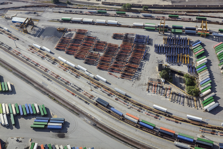 unloading: Aerial of unloading container trailers at railway terminal, USA. Railroad tracks, containers, trailers