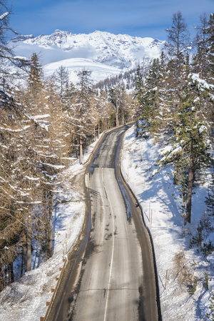 winter tires: Asphalt curved road in high Alp mountains, winter season Stock Photo