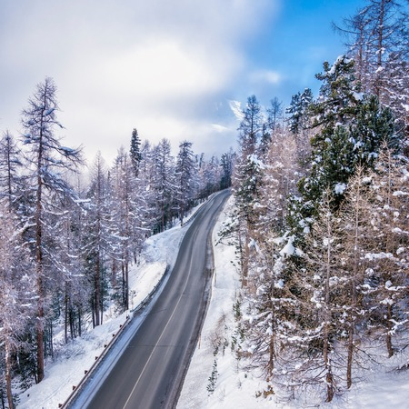 winter tires: Road leading to high snowy mountains behind fog, winter season Stock Photo
