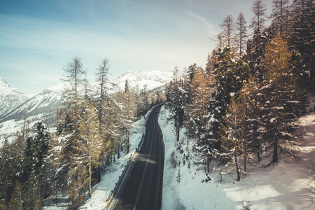 Asphalt road in high Alp mountains, winter season. Vintage colors Stock Photo