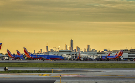 Southwest Airlines passenger airplanes waiting at terminal on Chicago Midway Airport at sunset. Downtown skyscrapers visible on horizon.