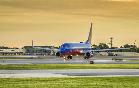 Southwest Airlines passenger airplane taxiing on runway in Chicago Midway Airport. Sunset clear sky condition. Editorial