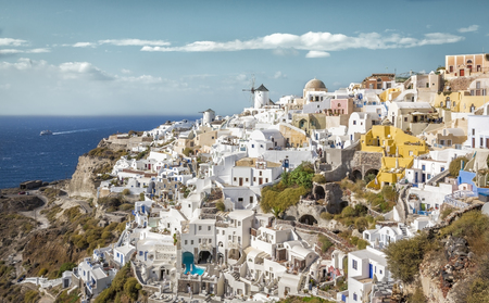 White cave houses on the cliff and famous windmill landmark, Santorini Island, Greece Stock Photo