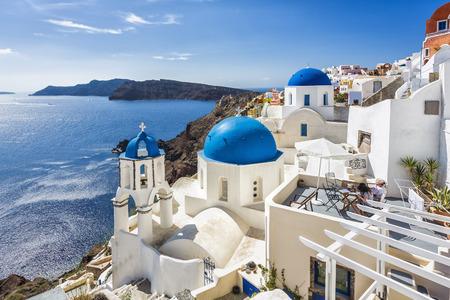 Santorini blue dome churches on the steep cliff, Greece. Caldera view. Stock Photo