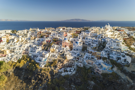 Aerial view of white houses on the steep cliff in Oia, Santorini Island, Greece