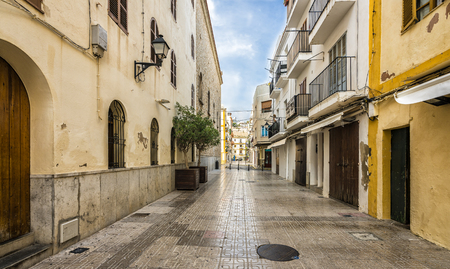 Typical empty street in old town of Ibiza, Balearic Islands, Spain. Morning light. Wide angle Stock Photo