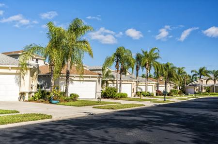 Casas típicas de la comunidad cerrada con palmeras y carretera de asfalto, sur de la Florida Foto de archivo - 93268890