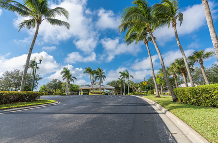 Guard entrance road to gated community with palms, South Florida Banque d'images