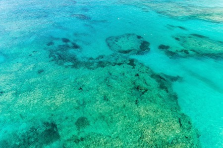 Aerial view of clear ocean water with coral reefs. Nature summer background