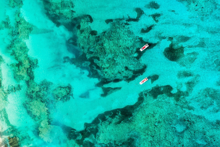 Aerial top view of two empty boats on bright ocean water with colar reefs