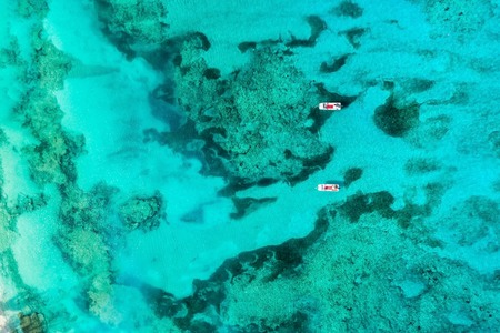 Top view of amazing turquoise ocean water with coral reefs and two boats. Aerial view