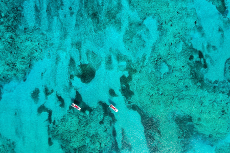 Aerial top view of turquoise clear ocean water with coral reefs and two boats Reklamní fotografie