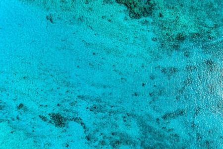 Top aerial view of blue bright ocean water with reefs. Nature summer background