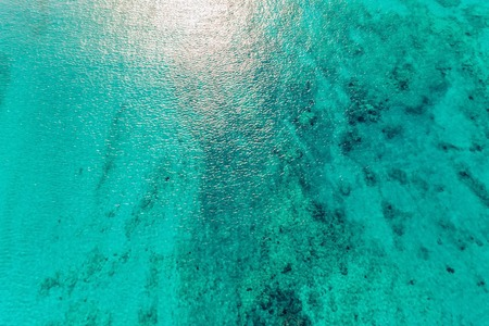 Aerial top view of clear ocean water with reefs and sunshine. Nature background Reklamní fotografie