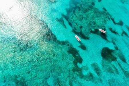 Blick von oben auf das klare Meerwasser mit Riffen und Booten. Natursommerhintergrund mit Sonnenschein Standard-Bild