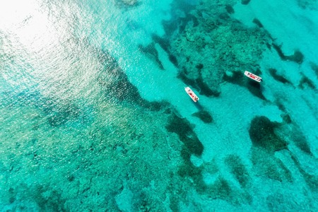 Top view of clear ocean water with reefs and boats. Nature summer background with sunshine
