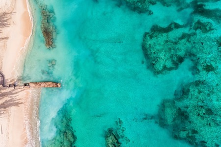 Amazing top aerial view of the beach and clear ocean water with coral reefs. Summer background