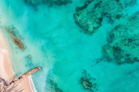 Beach top view with pier and clear Caribbean ocean water, coral reefs. Summer background