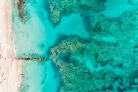 Beach with pier aerial top view. Caribbean ocean water, coral reefs. Summer background