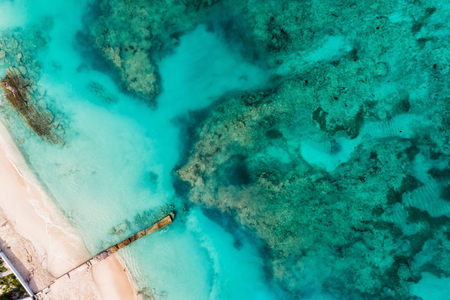 Beach with pier. Caribbean clear ocean water, coral reefs. Aerial view. Summer background