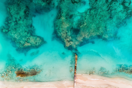 Top aerial view of the beach with pier and clear Caribbean ocean water, coral reefs. Summer background Reklamní fotografie