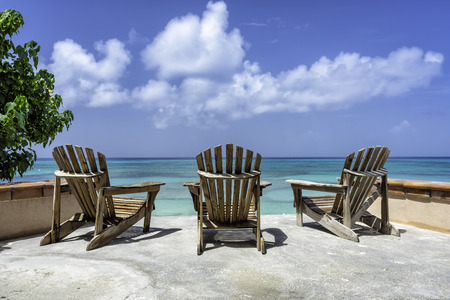 Wooden beach chairs facing the clear tropical ocean, low angle view