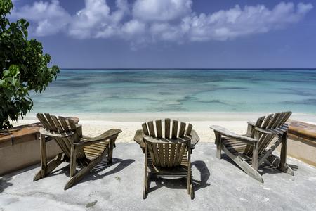 Wooden beach chairs facing the clear tropical ocean