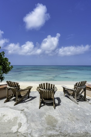 Wooden beach chairs in front of tropical ocean