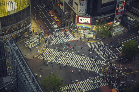 TOKYO, JAPAN - CIRCA APRIL 2017: Pedestrian scramble crosswalk in Shibuya, Tokyo at night. People crossing the street in business district