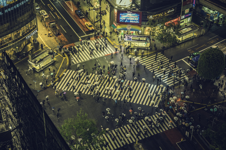 TOKYO, JAPAN - CIRCA APRIL 2017: Pedestrian scramble crosswalk in Shibuya, Tokyo. High angle view of people crossing the street in business district. Vintage tone
