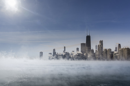 Sun above Chicago Downtown and Lake Michigan covers by fog from winter polar vortex