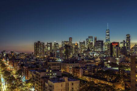 Lower Manhattan skyscrapers at sunset. Street with cars and Brooklin Bridge on horizon, New York City