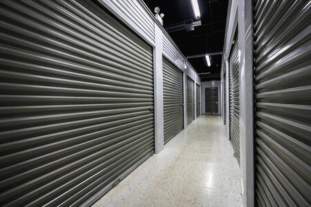 Pasillo largo de la instalación de almacenamiento. Puertas de garaje con luz