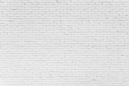 Brick painted white wall with delicate shadows, can be used for texture or background