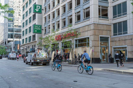 CHICAGO, ILLINOIS - MAY 31, 2019: Streets with people watching and volunteers after protesters march in downtown Chicago. Many storefronts with broken windows.