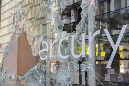 CHICAGO, ILLINOIS - MAY 31, 2019: Broken window storefront after protesters march demonstrations against police in Chicago Editorial