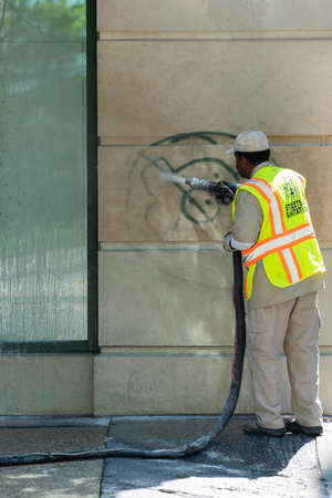 CHICAGO, ILLINOIS - MAY 31, 2019: City worker washing out graffiti from the building wall made by protesters night before during Chicago justice march