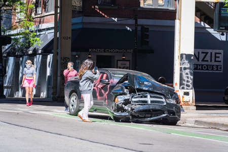 CHICAGO, ILLINOIS - MAY 31, 2019: People making pictures of the car wreckage day after after justice march against police in Chicago