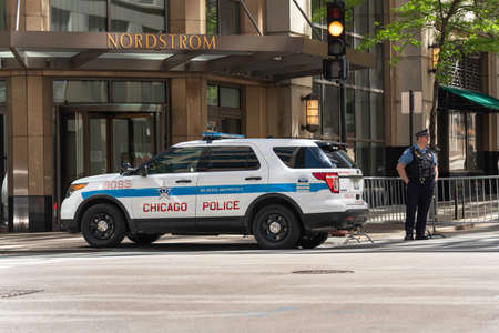 CHICAGO, ILLINOIS - MAY 31, 2019: Police car by Nordstrom store entrance, day after protests escalated into riots in the Chicago Loop overnight.